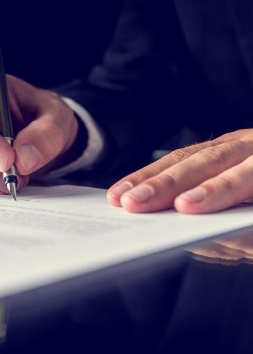 Mann mit Vertrag am Schreibtisch - Dr. Gabriella Peterfy - Rechtsanwalt für Vertragsrecht